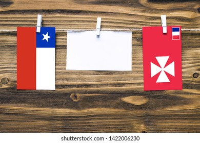 Hanging flags of Chile and Wallis And Futuna attached to rope with clothes pins with copy space on white note paper on wooden background.Diplomatic relations between countries.