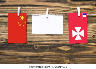 Hanging flags of China and Wallis And Futuna attached to rope with clothes pins with copy space on white note paper on wooden background.Diplomatic relations between countries.