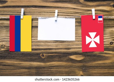 Hanging flags of Colombia and Wallis And Futuna attached to rope with clothes pins with copy space on white note paper on wooden background.Diplomatic relations between countries.