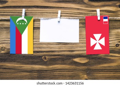 Hanging flags of Comoros and Wallis And Futuna attached to rope with clothes pins with copy space on white note paper on wooden background.Diplomatic relations between countries.
