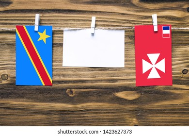 Hanging flags of Congo and Wallis And Futuna attached to rope with clothes pins with copy space on white note paper on wooden background.Diplomatic relations between countries.