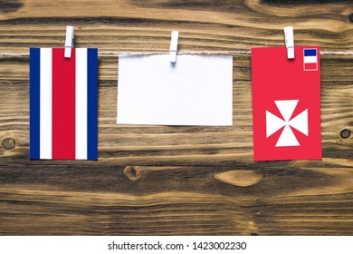 Hanging flags of Costa Rica and Wallis And Futuna attached to rope with clothes pins with copy space on white note paper on wooden background.Diplomatic relations between countries.