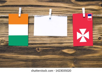Hanging flags of Cote D'Ivoire and Wallis And Futuna attached to rope with clothes pins with copy space on white note paper on wooden background.Diplomatic relations between countries.
