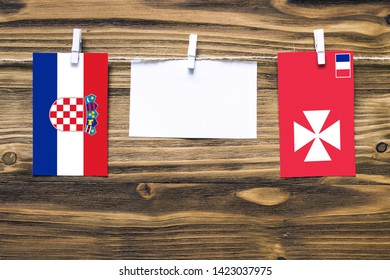 Hanging flags of Croatia and Wallis And Futuna attached to rope with clothes pins with copy space on white note paper on wooden background.Diplomatic relations between countries.