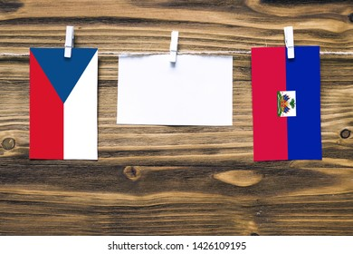 Hanging flags of Czech Republic and Haiti attached to rope with clothes pins with copy space on white note paper on wooden background.Diplomatic relations between countries.