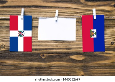 Hanging flags of Dominican Republic and Haiti attached to rope with clothes pins with copy space on white note paper on wooden background.Diplomatic relations between countries.