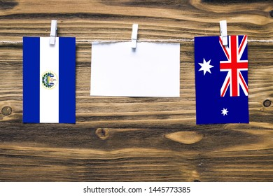 Hanging flags of El Salvador and Heard and Mcdonald Islands attached to rope with clothes pins with copy space on white note paper on wooden background.Diplomatic relations between countries.