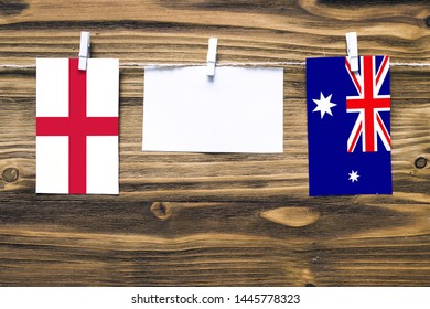 Hanging flags of England and Heard and Mcdonald Islands attached to rope with clothes pins with copy space on white note paper on wooden background.Diplomatic relations between countries.