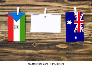 Hanging flags of Equatorial Guinea and Heard and Mcdonald Islands attached to rope with clothes pins with copy space on white note paper on wooden background.Diplomatic relations between countries.