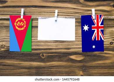 Hanging flags of Eritrea and Heard and Mcdonald Islands attached to rope with clothes pins with copy space on white note paper on wooden background.Diplomatic relations between countries.