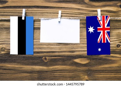 Hanging flags of Estonia and Heard and Mcdonald Islands attached to rope with clothes pins with copy space on white note paper on wooden background.Diplomatic relations between countries.