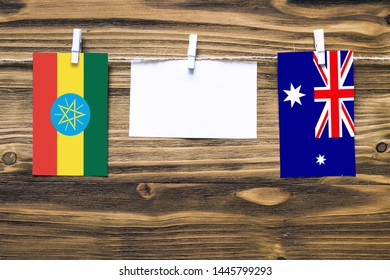 Hanging flags of Ethiopia and Heard and Mcdonald Islands attached to rope with clothes pins with copy space on white note paper on wooden background.Diplomatic relations between countries.