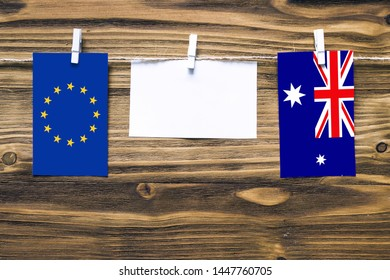 Hanging flags of European Union and Heard and Mcdonald Islands attached to rope with clothes pins with copy space on white note paper on wooden background.Diplomatic relations between countries.