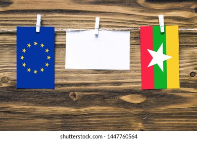 Hanging flags of European Union and Myanmar attached to rope with clothes pins with copy space on white note paper on wooden background.Diplomatic relations between countries.