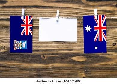 Hanging flags of Falkland Islands and Heard and Mcdonald Islands attached to rope with clothes pins with copy space on white note paper on wooden background.Diplomatic relations between countries.