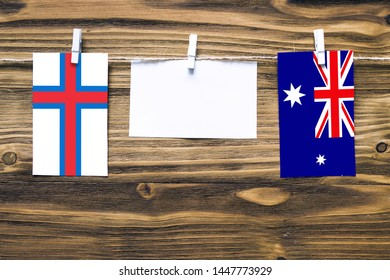 Hanging flags of Faroe Islands and Heard and Mcdonald Islands attached to rope with clothes pins with copy space on white note paper on wooden background.Diplomatic relations between countries.