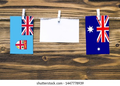 Hanging flags of Fiji and Heard and Mcdonald Islands attached to rope with clothes pins with copy space on white note paper on wooden background.Diplomatic relations between countries.