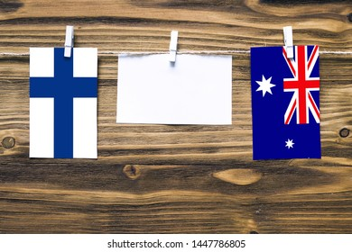Hanging flags of Finland and Heard and Mcdonald Islands attached to rope with clothes pins with copy space on white note paper on wooden background.Diplomatic relations between countries.