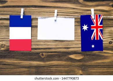 Hanging flags of France and Heard and Mcdonald Islands attached to rope with clothes pins with copy space on white note paper on wooden background.Diplomatic relations between countries.
