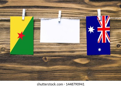 Hanging flags of French Guiana and Heard and Mcdonald Islands attached to rope with clothes pins with copy space on white note paper on wooden background.Diplomatic relations between countries.