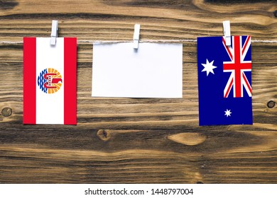 Hanging flags of French Polynesia and Heard and Mcdonald Islands attached to rope with clothes pins with copy space on white note paper on wooden background.Diplomatic relations between countries.