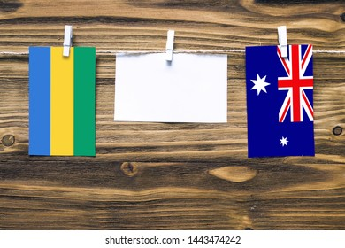 Hanging flags of Gabon and Heard and Mcdonald Islands attached to rope with clothes pins with copy space on white note paper on wooden background.Diplomatic relations between countries.