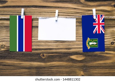 Hanging flags of Gambia and British Virgin Islands attached to rope with clothes pins with copy space on white note paper on wooden background.Diplomatic relations between countries.