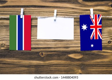 Hanging flags of Gambia and Heard and Mcdonald Islands attached to rope with clothes pins with copy space on white note paper on wooden background.Diplomatic relations between countries.
