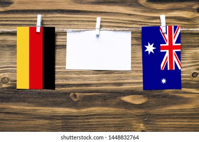 Hanging flags of Germany and Heard and Mcdonald Islands attached to rope with clothes pins with copy space on white note paper on wooden background.Diplomatic relations between countries.