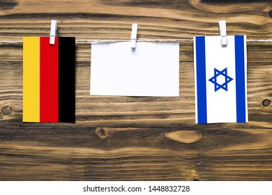 Hanging flags of Germany and Israel attached to rope with clothes pins with copy space on white note paper on wooden background.Diplomatic relations between countries.