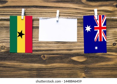 Hanging flags of Ghana and Heard and Mcdonald Islands attached to rope with clothes pins with copy space on white note paper on wooden background.Diplomatic relations between countries.
