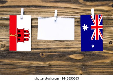 Hanging flags of Gibraltar and Heard and Mcdonald Islands attached to rope with clothes pins with copy space on white note paper on wooden background.Diplomatic relations between countries.