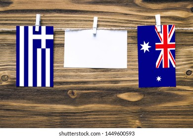 Hanging flags of Greece and Heard and Mcdonald Islands attached to rope with clothes pins with copy space on white note paper on wooden background.Diplomatic relations between countries.
