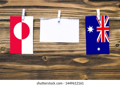 Hanging flags of Greenland and Heard and Mcdonald Islands attached to rope with clothes pins with copy space on white note paper on wooden background.Diplomatic relations between countries.