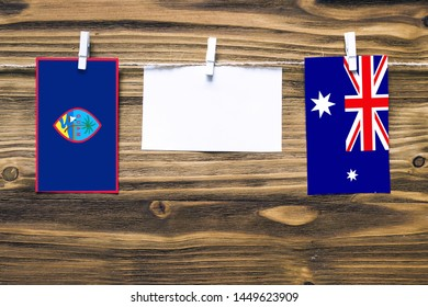 Hanging flags of Guam and Heard and Mcdonald Islands attached to rope with clothes pins with copy space on white note paper on wooden background.Diplomatic relations between countries.