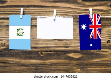 Hanging flags of Guatemala and Heard and Mcdonald Islands attached to rope with clothes pins with copy space on white note paper on wooden background.Diplomatic relations between countries.