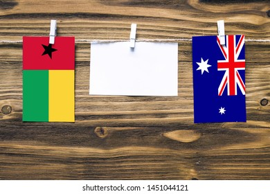 Hanging flags of Guinea Bissau and Heard and Mcdonald Islands attached to rope with clothes pins with copy space on white note paper on wooden background.Diplomatic relations between countries.