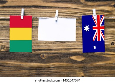 Hanging flags of Guinea and Heard and Mcdonald Islands attached to rope with clothes pins with copy space on white note paper on wooden background.Diplomatic relations between countries.