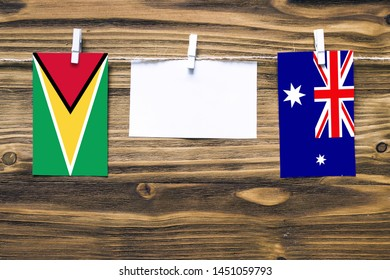 Hanging flags of Guyana and Heard and Mcdonald Islands attached to rope with clothes pins with copy space on white note paper on wooden background.Diplomatic relations between countries.