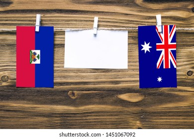 Hanging flags of Haiti and Heard and Mcdonald Islands attached to rope with clothes pins with copy space on white note paper on wooden background.Diplomatic relations between countries.