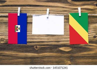 Hanging flags of Haiti and Republic Of The Congo attached to rope with clothes pins with copy space on white note paper on wooden background.Diplomatic relations between countries.