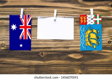 Hanging flags of Heard and Mcdonald Islands and Saint Pierre And Miquelon attached to rope with clothes pins with copy space on white note paper on wooden background.Diplomatic relations.