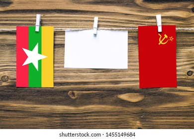 Hanging flags of Myanmar and Soviet Union attached to rope with clothes pins with copy space on white note paper on wooden background.Diplomatic relations between countries.