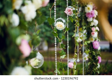 Hanging glass ball, bubble with white and pink roses hanging from the wedding arch with green plants and leaves. Wedding decoration, stylish floristry