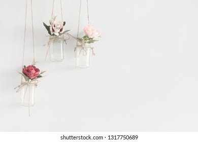 Hanging glass jars with flowers interior wall decoration with copy space for text.