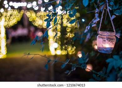 Hanging glasses with candles at night wedding party on garden. Illuminated bokeh background