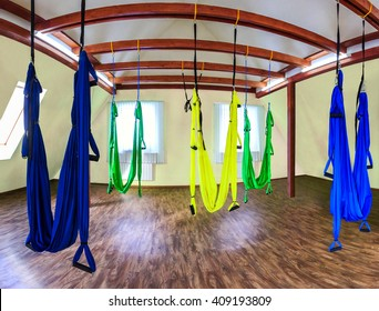 Hanging hammocks in gym for aerial (fly) yoga. Interior for sport