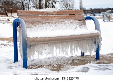 hanging icicles on vacant blue park bench in winter