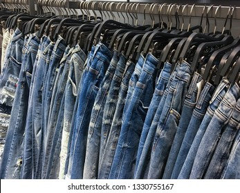 Hanging in interior of different blue jeans in store