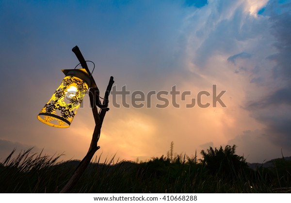 the hanging lantern on the wooden stick in the forest at dusk